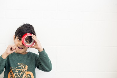 a boy looking through shiny red roll of tape