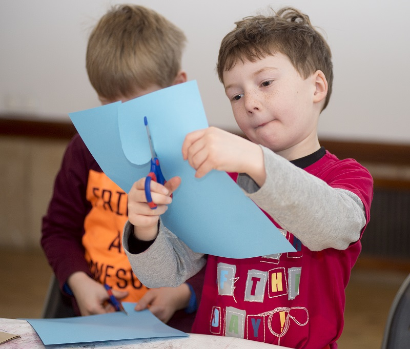 two boys cutting paper